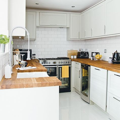 White kitchen with wooden worktops and metro tiles