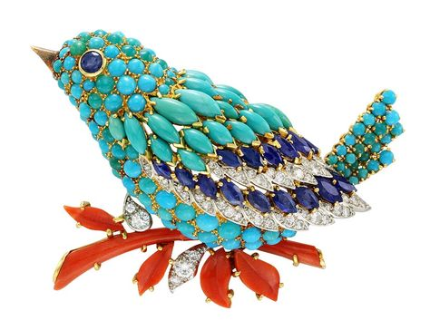 A colourful Van Cleef & Arpels bird clip in platinum and yellow gold, set with sapphires, turquoise, coral and diamonds, created in 1963.