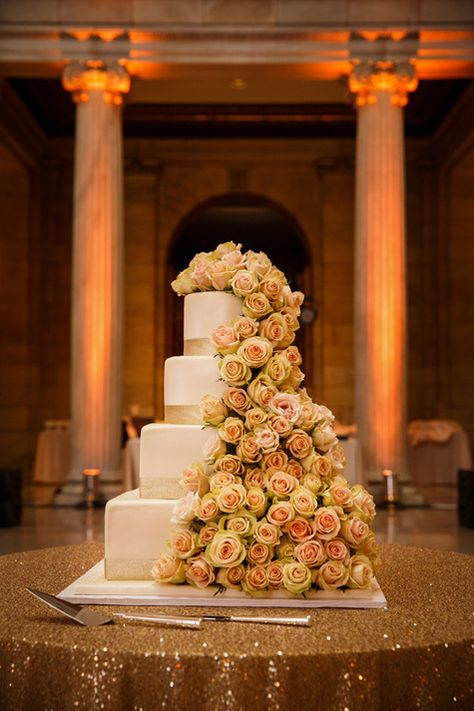 Four-Tiered Ivory Wedding Cake with Cascading Floral Decor | Michael Angelo's Bakery | Genevieve Nisly Photo | TheKnot.com