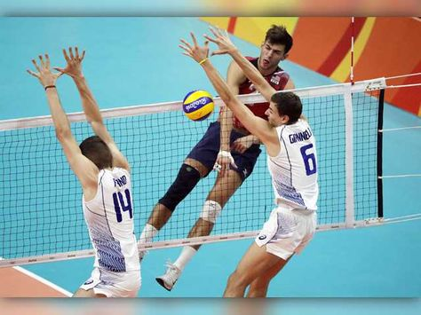 United States' Aaron Russell, top right, spikes the ball as Italy's Simone Giannelli (6) and Matteo Piano block during a men's preliminary volleyball match at the 2016 Summer Olympics in Rio de Janeiro, Brazil, Tuesday, Aug. 9, 2016. The Associated Press