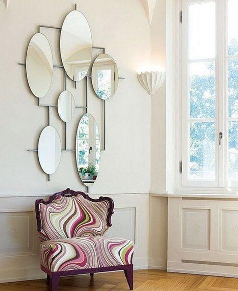 une compositions de miroirs décoratifs au-dessu d'un fauteuil vintage