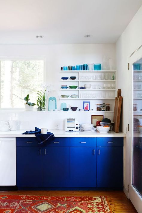 Bright blue kitchen cabinetryhelps ground the white-walledspace.