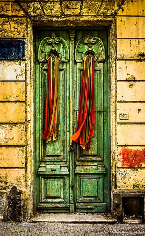 Green doors with colorful red orange streamers in Montevideo, Uruguay