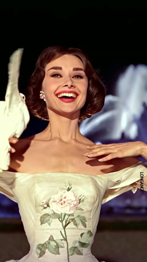 Audrey Hepburn posing as a model in a beautiful 50s white dress in the classic movie Funny Face.