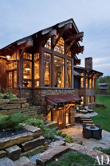 """""""It was important to me that the house look refined,"""" says the client. """"It's not our chalet. It's not our rustic cabin in the woods. It's our home."""" The rear elevation and patios   archdigest.com"""