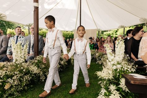 We love these pageboys in their adorable outfits with gray pants, white button-downs, light pink linen bow ties, and leather suspenders at this spring rustic chic tented wedding ceremony. Click through for more rustic wedding ideas! #rusticwedding #pageboyoutfits #tentedwedding #rusticweddingceremony #groomsmenoutfits