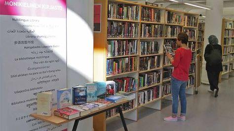 2016 HelMet reading challenge... Kuva kirjastosta, etualalla kirjaston kyltti, taustalla nainen hyllyn ääressä.