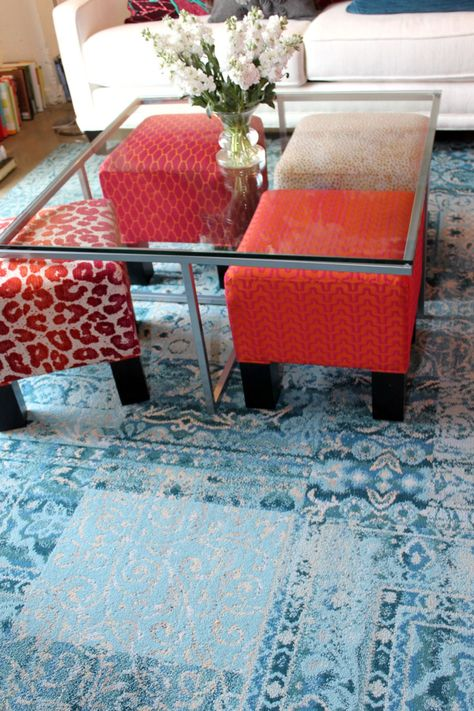 Colorful ottomans under a clear table when not being used. Cool idea!