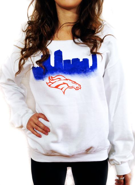 Broncos fans! This sweatshirt is a super comfortable, white, off the shoulder top with a hand painted Denver skyline and Broncos logo! Mens