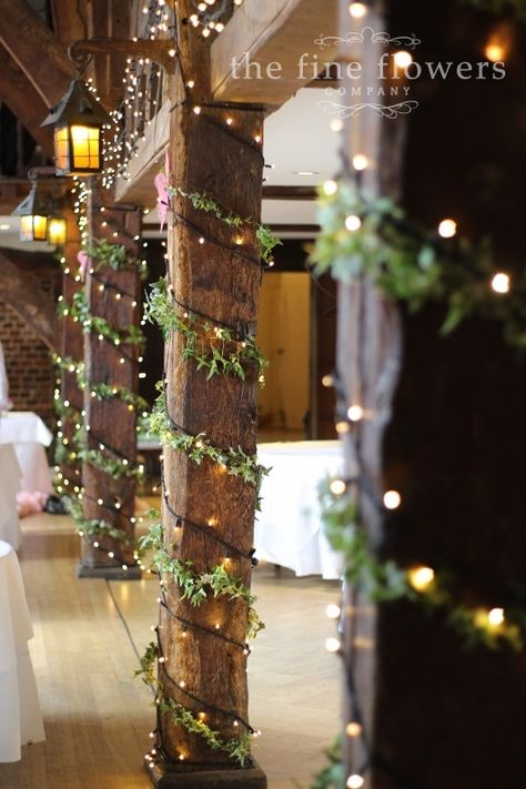 The pillar uprights at the Tithe Barn in great Fosters, decorated with ivy and fairy lights.  From wedding reception at Great Fosters