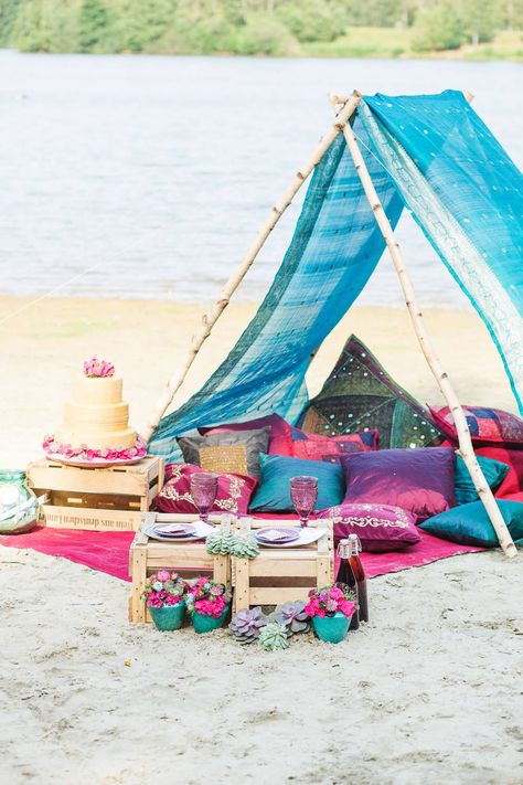 A tipi, tent made up of a brightly coloured sari & sumptuous velvet & satin cushions with wooden crates as tables - Image by Julias Chick Fotografie - A Lakeside boho hippie inspired styled shoot with bright coloured tipi, cushions, decor & flowers for a relaxed unconventional wedding by the sea.