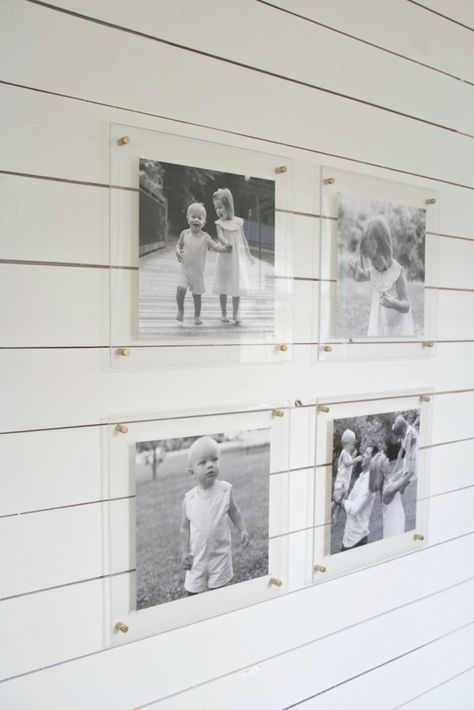 Because lucite frames are transparent, the wall behind them has the power to completely transform the look of whatever they display. Black and white family photos that might look bold and modern against a dark gray wall, appear beachy and nostalgic when hung in a shiplap mudroom on Crisp Interiors.