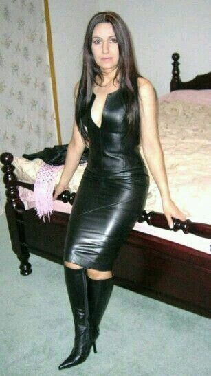 Booted lady in a tight black leather midi dress with a tempting deco Ledermode