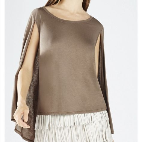 BCBG Maxazria Vinessa Poncho Cape Top Elevate your collection of tees with this poncho cape constructed top for all-day sophisticated ease. Wear yours tucked into a fringe skirt and slip on metallic booties for total urban sophistication. Round neckline. Short sleeves. Cape construction. Asymmetrical hemline. Slight relaxed fit. Self: Rayon jersey. Machine Wash. BCBGMaxAzria Tops Blouses