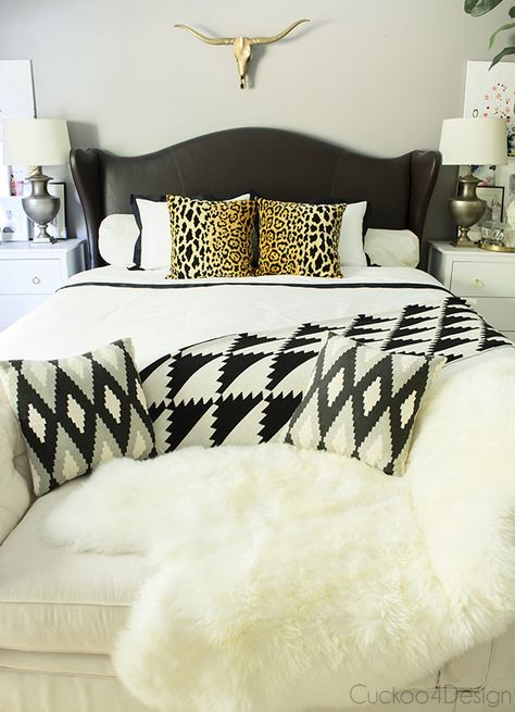 neutral black and white bedroom with brass and leopard accents, fur, leather studded wingback bed, button tufted chaise/end of the bed bench- Cuckoo4Design
