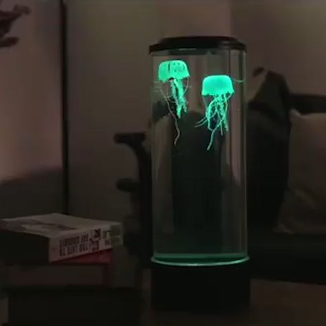 """LED-lighted desktop aquarium has two synthetic jellyfish that provide mesmerizing ambiance, just like their real counterparts.  The aquarium has 18 LEDs (six each of red, blue, and green) that automatically change color, causing both jellyfish to """"react"""" by glowing yellow, purple, aquamarine, blue, and red as they float within gentle currents generated by the unit's silent, integrated motor."""