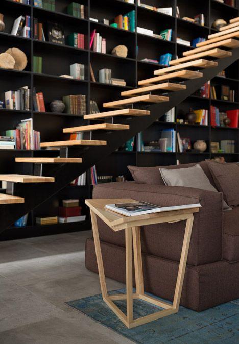 A staircase runs up alongside a six-metre-high bookshelf inside this house in Ukraine.