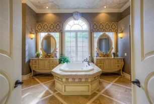 mediterranean master bathroom with wall sconce, arched