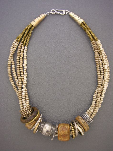 by Anne Holland | A treasure necklace composed of Indonesian and Tibetan bone rings, Fulani wedding rings, and other rings made from sterling silver and bronze. The key piece in this creation is the rare antique silver bead in the middle from the silversmiths of Oman. On five strands of antique white glass beads from Indonesia,with brass heishi, bronze cones, and a sterling silver hook and eye clasp | Sold