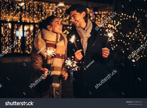 Couple holding Christmas sprinkler outdoors #Ad , #sponsored, #holding#Couple#Christmas#outdoors