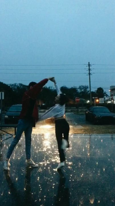 Teen couple dancing in the rain. Boyfriend is twirling his girlfriend in the light of the car's headlights - male and female - young love - carefree - careless - freedom - high school - whimsical - emotions - people - action
