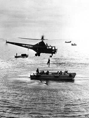 A hovering US Marine helicopter picks up personnel from a landing barge in the harbour at Inchon