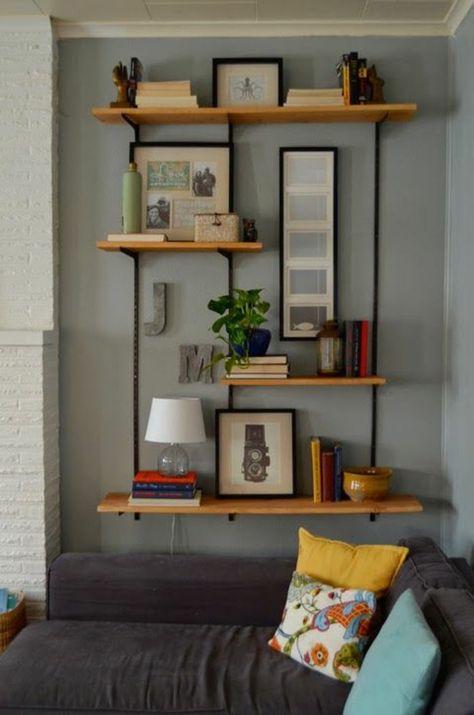 canapé gris dans le salon, murs gris, décoration murale, étagère en bois en fer noir