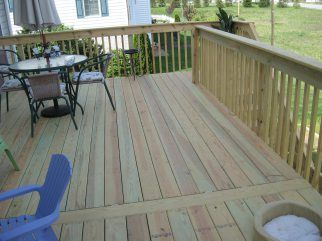 This High Deck Was Built With Pressure Treated Wood And Features A Landing Halfway Up The Stairs To Break U Treated Wood Deck Wood Deck Pressure Treated Wood