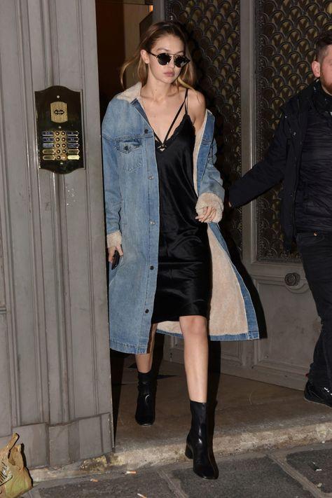 Gigi Hadid in a black Nili Lotan slip dress, Sandro black booties, a long jean jacket, and Illesteva sunglasses