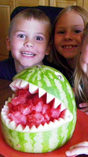 Watermelon Shark ala Fruit Carving Arrangements and Food Garnishes...    Make food fun!!!  THIS IS SOOOOOO EASY and fun to do.  Great project to do with the kids, just a small amount of cutting and lots of melon balling that they can do!  EASY PEASY