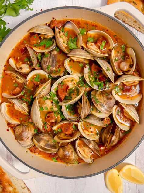 These littleneck clams steamed in white wine, surrounded by aromatics, and rich in umami from chorizo, will be the most flavorful clams you'll eat. The zesty clam and chorizo broth is deliciously soaked up with your favorite bread or pasta. #clams #steamedclams #clamsandchorizo #littleneckclams #clamrecipe #spicyclams #seafood #seafoodrecipe #chorizo