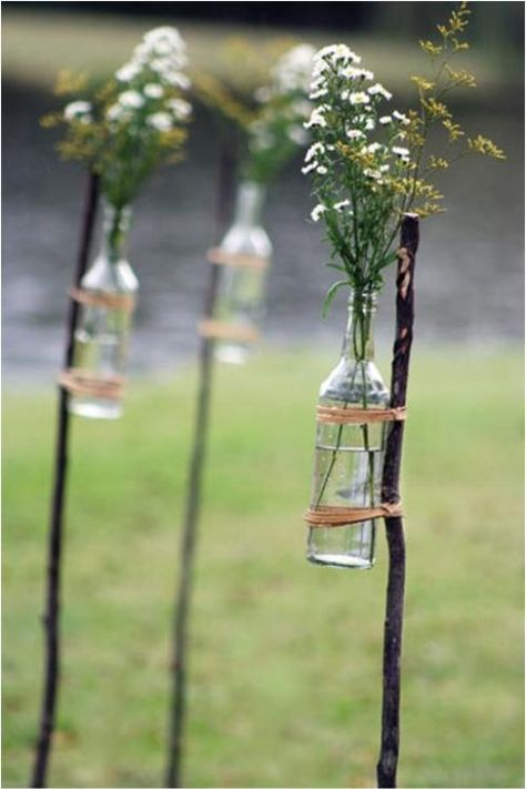 I've seen mason jars hung from sticks, lanterns, and now bottles attached to them - I think all are great ideas for easy decorations in a garden - a way of giving a sense of space in an outdoor venue.