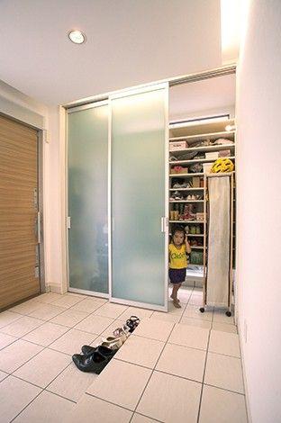 玄関の壁一面にシューズクロークを設置 内部には地窓を横長に設け 半透明の扉から光が透けて玄関に明るさをもたらすしくみになっている 地窓の上に シューズクローゼット 扉 シューズクローゼット 収納 クローゼット 収納
