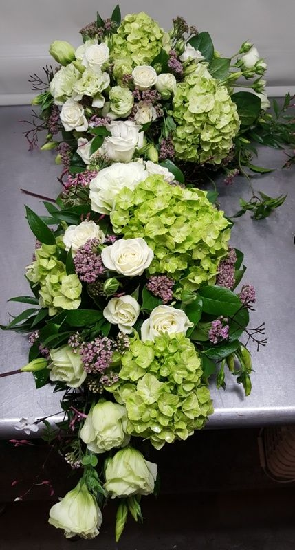 A two-piece corner flower arrangement for a wedding arch in shades of white and green with pink accents from Seasonal Celebrations.