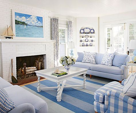 In this sunny living room, a white and blue scheme lays a foundation for cottage style. A white brick fireplace and corner built-in hutch bring architectural detail to the space. French doors let in light and open up to the backyard. Gingham and a leafy pattern, both in blue and white, advance the room's cottage style, while the painting and ship on the mantel infuse beachside flair.
