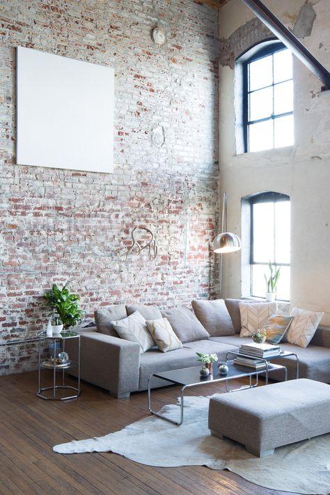 Salon de charme avec une magnifique hauteur sous plafond et un mur en briques.
