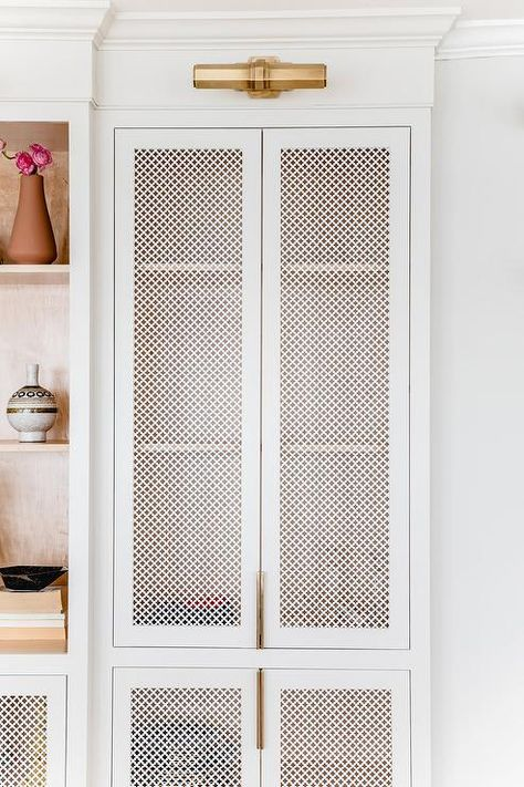 White quatrefoil metal cabinet doors illuminated by brass picture lights beside white built-in cabinets. Flur Design, Home Design, Home Interior Design, Built In Cabinets, Metal Cabinets, Transitional Living Rooms, Cabinet Doors, Cabinet Fronts, Built Ins