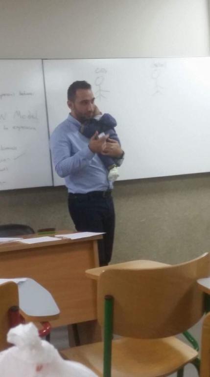 استاذ جامعي في لبنان يحمل طفل رضيع اثناء القاء المحاظرة اخبار العراق Decor Furniture Desk