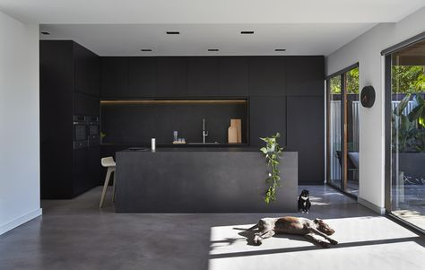 M House is a minimalist house located in Melbourne, Australia, designed by DKO. The kitchen space features blacked out custom cabinetry with a black kitchen island that allows for seating and serving. (2)