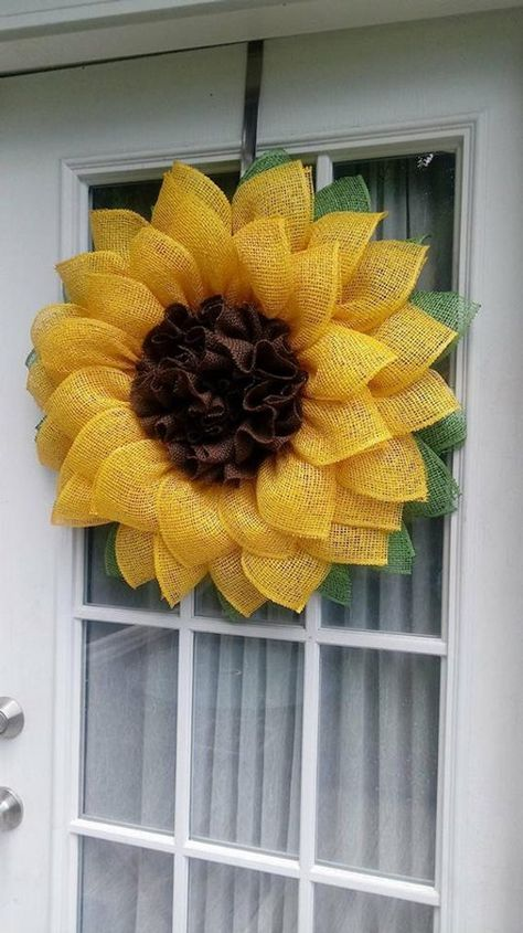 Beautiful Sunflower Wreath made from poly burlap and natural burlap. Two rows of sunny yellow petals, backed by lime green leaves. The center, is a darling ruffle, made with a natural chocolate burlap fabric. This wreath measures 27 around. The wreath has been sprayed with a protectant to help guard
