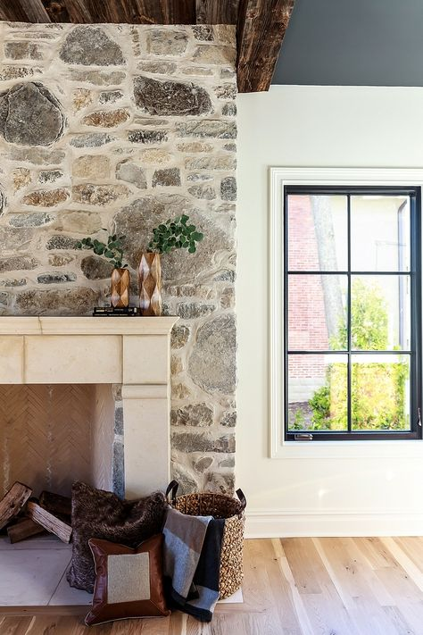 Stone Fireplace This dramatic stone fireplace creates quite the focal point in this family room Stone Fireplace with reclaimed wood beamed ceiling and Limenstone mantel #stonefireplace #fireplace #limestonemantel