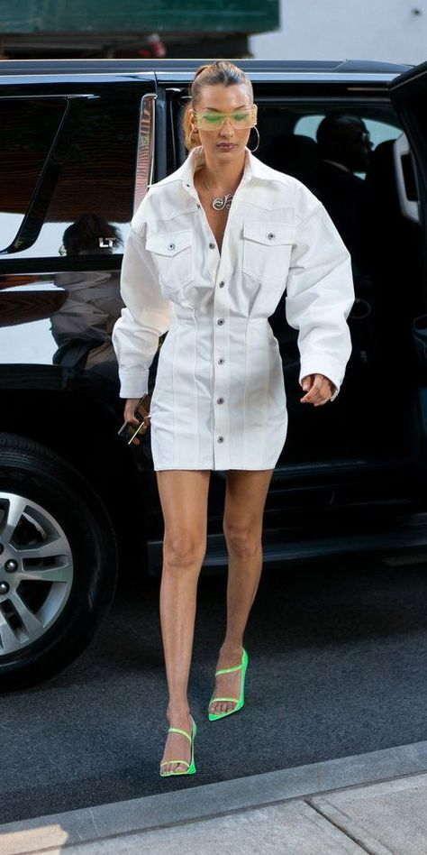 Look of the Day -  Bella Hadid stunted in a head-to-toe Fenty look, which included a white denim dress and matching neon glasses and pointed-toe sandals. A fancy pendant necklace by Nigora Tabayer completed her winning outfit. Source by sydnesummer  -