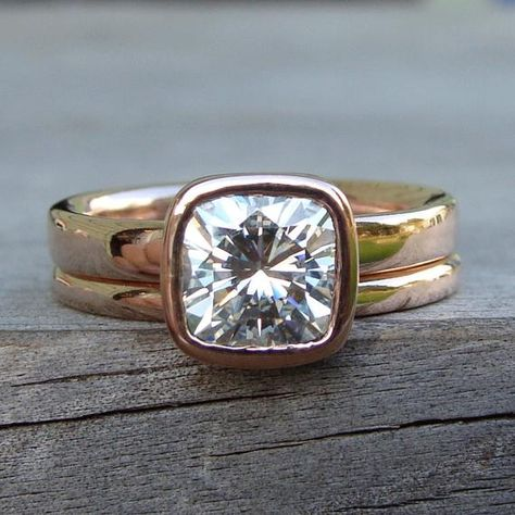This lovely set features a bezel set cushion cut Forever One G-H-I moissanite (7mm; equivalent in size to a 1.8 carat diamond) on a 3mm wide comfort-fit engagement ring, paired with a 2mm round matching band. All of the metal used in the construction of this ring is 14k rose gold from recycled