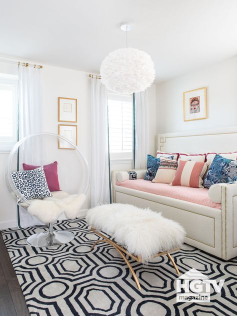 A black and white rug, a white pendant and chic accessories make this white bedroom super cozy. See more on HGTV.com.