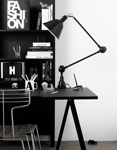Monochrome home office decor with large task lamp and design books