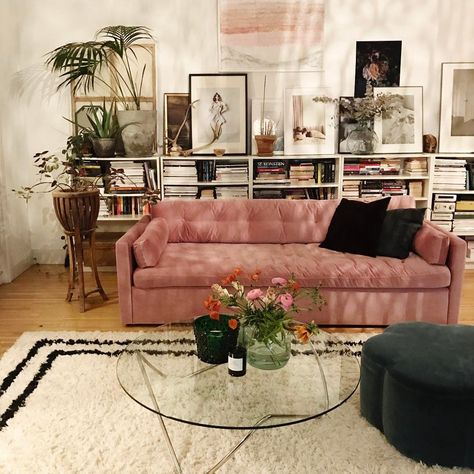 Low shelving with books and art displayed for living room front wall on each side of window. 20 Gorgeous Ways to Display Art That Are Better Than a Gallery Wall