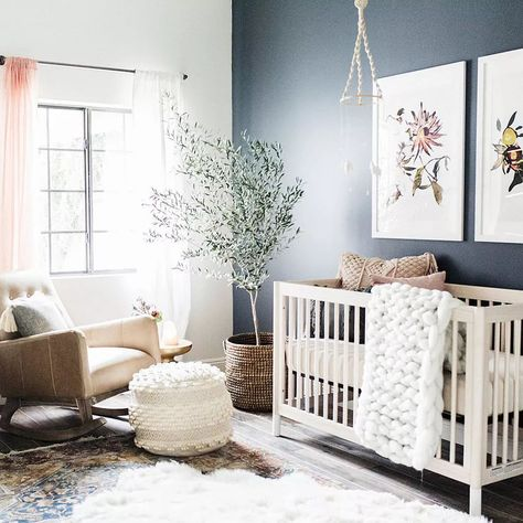 Neutral nursery with muted navy accent wall.