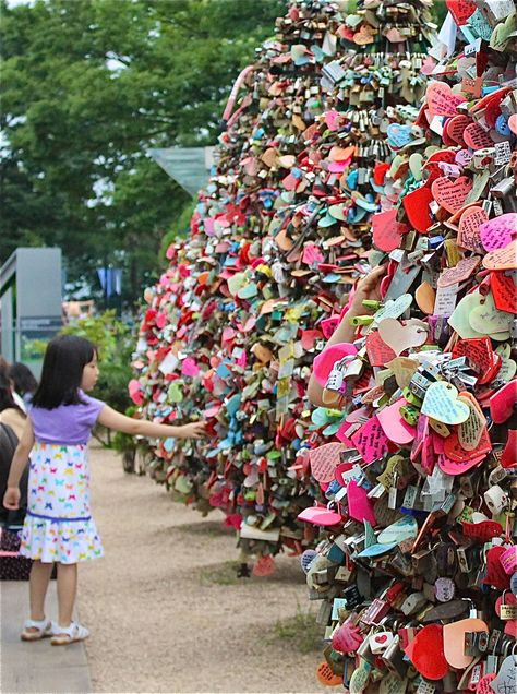 Namsan Tower! Pete and I have a lock here - A young girl reaches out for one of the hundreds of thousands of love locks placed along fenses atop Namsan Tower in Seoul