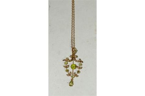 A 9ct gold Art Nouveau style pendant piece set with peridot and seed pearls, suspended on a 9ct g