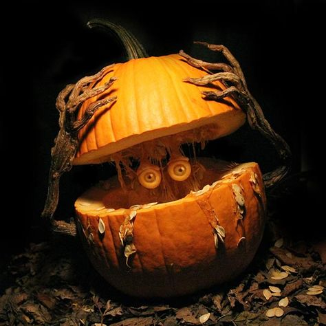 pumpkin sliced in half horizontally with two branch-looking hands lifting the top half of the pumpkin to reveal eyes inside the pumpkin, from the 2015 This Old House Pumpkin Carving Contest